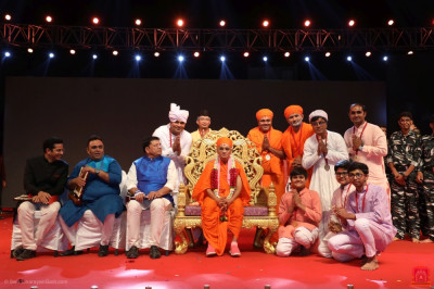 His Divine Holiness Acharya Swamishree Maharaj presents a medal to each disciple from Surat who took part in the drama performances