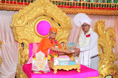 His Divine Holiness Acharya Swamishree Maharaj blesses the medical doctors for their services and presents a memento, a shawl and garland of flowers