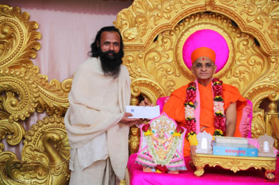 His Divine Holiness Acharya Swamishree Maharaj presents a cheque with a donation to Shree Akileshwar Maharaj