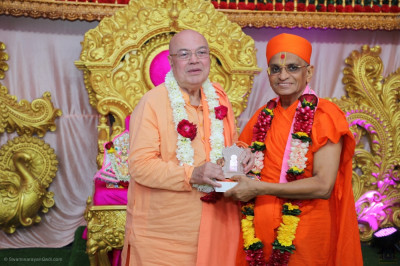 His Divine Holiness Acharya Swamishree Maharaj presents the memento of the grand five day festival to Swami Adhyatmananda Maharaj