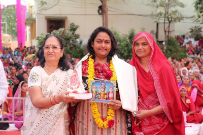 Sankhya Yogi lady and a disciples present a praasd shawl, a garland of flowers and a murti memento to Bijal Patel - Mayor of the Ahmedabad Municipal Corporation (AMC)