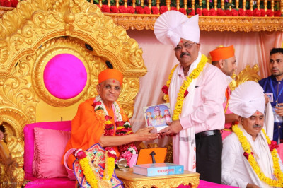 His Divine Holiness Acharya Swamishree Maharaj presents a prasad paag, a prasad shawl, a garland of flowers and a murti memento to - Amul Bhatt standing committee