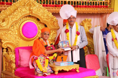 His Divine Holiness Acharya Swamishree Maharaj presents a prasad paag, a prasad shawl, a garland of flowers and a murti memento to Asit Vohra - former Mayor of Ahmedabad