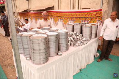 Disciples ensure plates, bowls and spoons are ready for afternoon prasad lunch