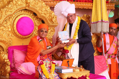 His Divine Holiness Acharya Swamishree Maharaj presents a prasad paag, prasad shawl, a garland of flowers and murti memento to Shankar Shivagela previous chief minister central textile minister
