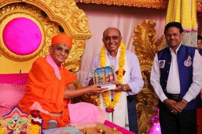 His Divine Holiness Acharya Swamishree Maharaj blesses the disciple