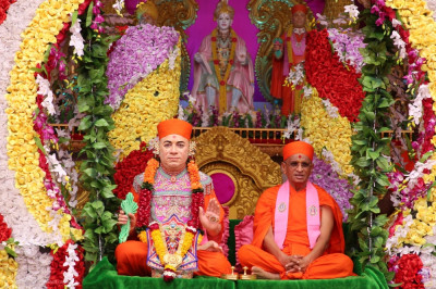 Divine darshan of His Divine Holiness Acharya Swamishree Maharaj with Jeevanpran Shree Muktajeevan Swamibapa seated on the delightfully decorated swing