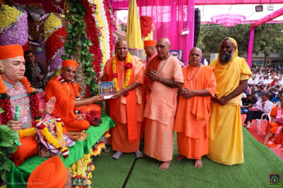 His Divine Holiness Acharya Swamishree Maharaj blesses the honoured guests and presents a murti memento