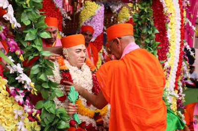 His Divine Holiness Acharya Swamishree Maharaj presents a garland of flowers to Jeevanpran Shree Muktajeevan Swamibapa