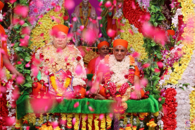 Jeevanpran Shree Muktajeevan Swamibapa and Acharya Swamishree Maharaj bless all seated on the delightful swing as sants shower flower petals