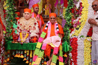 Disciples adorn a huge garland on His Divine Holiness Acharya Swamishree Maharaj