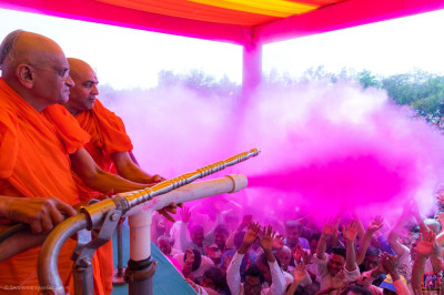 His Divine Holiness Acharya Swamishree Maharaj sprays all disciples in pink