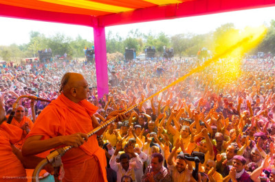 His Divine Holiness Acharya Swamishree Maharaj sprays all disciples in yellow