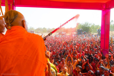 His Divine Holiness Acharya Swamishree Maharaj sprays all disciples in red