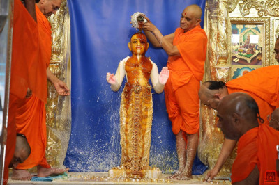 His Divine Holiness Acharya Swamishree Maharaj bathes Lord Shree Swaminarayan in the five nectars and gold and silver flower petals
