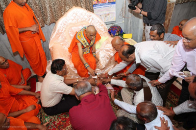 His Divine Holiness Acharya Swamishree Maharaj and disciples bath the lotus feet of the Lord in the five nectars