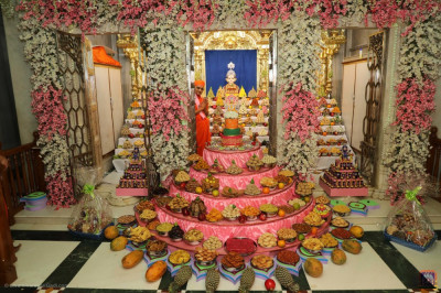 Divine darshan of His Divine Holiness Acharya Swamishree Maharaj with Lord Shree Swaminarayan and the magnificent grand annakut of sweet and savoury items offered to the Lord