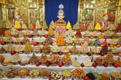 Divine darshan of Lord Shree Swaminarayan dining on the grand annakut of sweet and savoury items