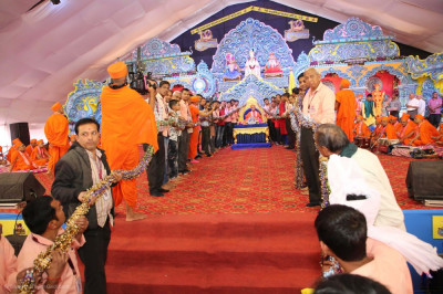 Disciples present a huge garland to His Divine Holiness Acharya Swamishree Maharaj
