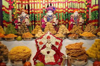 Divine darshan of the Lord dining on the grand annakut of delicious sweet and savoury items
