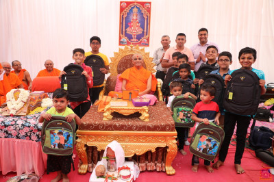 His Divine Holiness Acharya Swamishree Maharaj blesses disciples who have sponsored the bags for the children, and the children with their bags