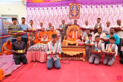 His Divine Holiness Acharya Swamishree Maharaj blesses disciples who carry gifts for the Lord
