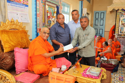 His Divine Holiness Acharya Swamishree Maharaj and disciples present the donation to the village cow shelter for the welfare of the cows