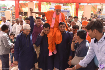 Disciples carry His Divine Holiness Acharya Swamishree Maharaj into the grand assembly