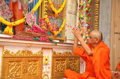 His Divine Holiness Acharya Swamishree Maharaj showers flower petals at the divine lotus feet of the Lord