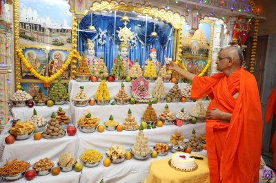 His Divine Holiness Acharya Swamishree Maharaj offers cake to the Lord