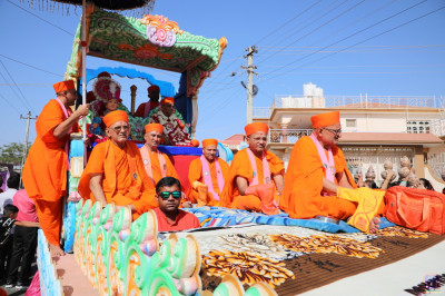 The float proceeds through the streets of the village