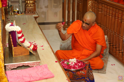 His Divine Holiness Acharya Swamishree Maharaj showers fragrant fresh flower petals at the divine lotus feet of the Lord