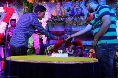 Disciples offer cake to His Divine Holiness Acharya Swamishree Maharaj