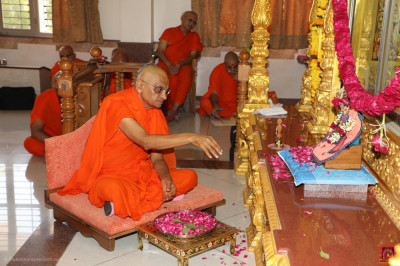 His Divine Holiness Acharya Swamishree Maharaj showers fresh fragrant flower petals at the divine lotus feet of the Lord
