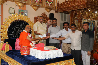 His Divine Holiness Acharya Swamishree Maharaj and disciples present the cheque to local charitable organisations