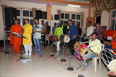 Sants and talented disciples and musicians perform devotional songs during raas