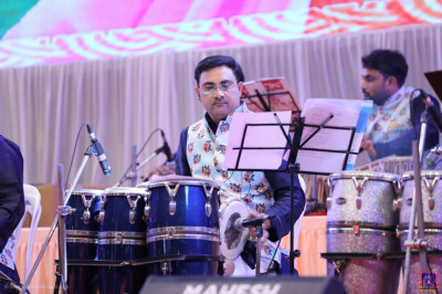 Percussion instrument performers accompany devotional song performances