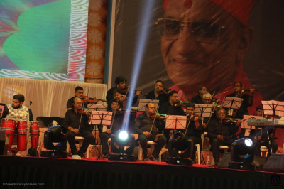 The violin section performs during the devotional concert