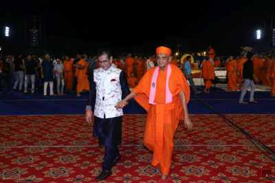 The disciple escorts His Divine Holiness Acharya Swamishree Maharaj to the stage