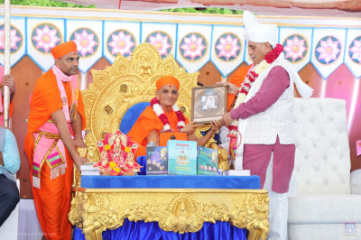 Acharya Swamishree Maharaj presents the memento of the grand festival to Chief Minister of Gujarat Vijay Rupani