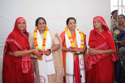 Sankhya Yogi ladies present prasad shawl, a garland of flowers and prasad to Maltiben Maheshwari and Nimaben Acharya  both Gujarat Legislative Members