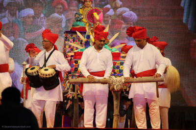 Disciples pull a traditional Ox kart with Jeevanpran Shree Abji Bapashree seated onto the stage and traditional tabla and hand cymbals are performed