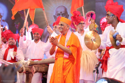 Divine darshan of Acharya Swamishree Maharaj joins disciples on stage during the finale performance of the evening