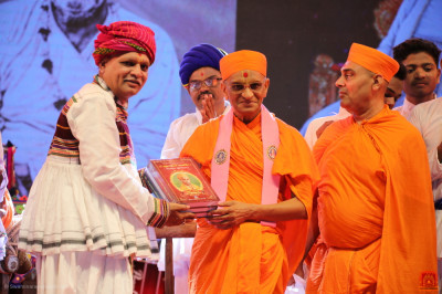 Acharya Swamishree Maharaj presents the divine scripture publications to the honoured guest