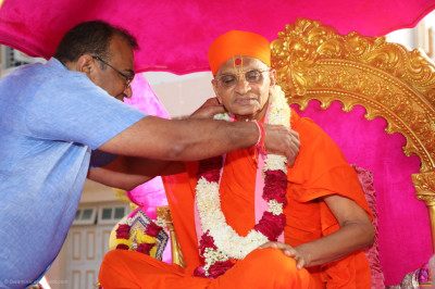 Disciples present a garland of white and red flowers to Acharya Swamishree Maharaj