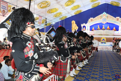 Shree Muktajeevan Swamibapa Pipe Band London perform in two flanks inside the grand assembly awaiting the arrival of His Divine Holiness Acharya Swamishree Maharaj seated on the golden chariot