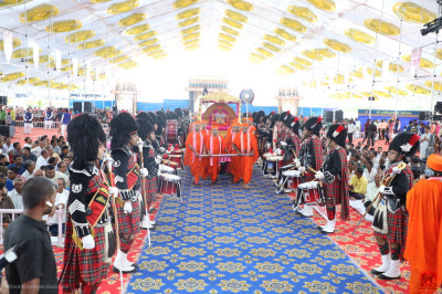 Sants pull the golden chariot towards the stage as Shree Muktajeevan Swamibapa Pipe Band London perform