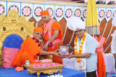 Acharya Swamishree Maharaj blesses the honoured guest who is associated with the sports ground that is being used for the grand assembly, with a prasad paag, shawl, a garland of flowers, prasad, and a memento of the grand festivals