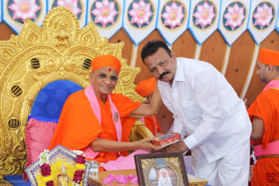 Acharya Swamishree Maharaj blesses the honoured guest with prasad