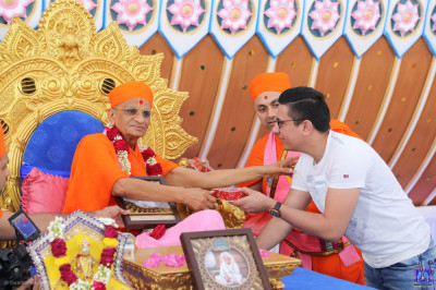 Acharya Swamishree Maharaj bless the honoured guest and presents prasad